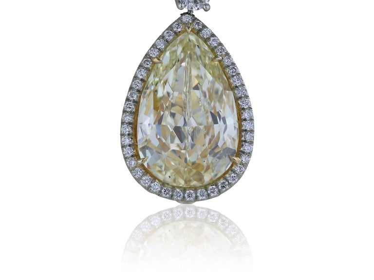 These stunning custom made platinum diamond drop earrings feature two pear shape Canary yellow diamonds weighing approximately 14.50cts. The center diamonds have a halo of white diamonds, there are two round brilliant diamonds diamonds set above