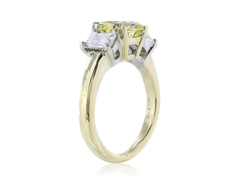 Three stone engagement ring of 1 Fancy Yellow radiant cut diamond weighing 1.66 carats, measuring 7.19 x 7.11 x 3.95 millimeters, with a clarity of VS1, flanked by two radiant cut diamonds weighing .84 carats with a color and clarity of G VS1-VS2