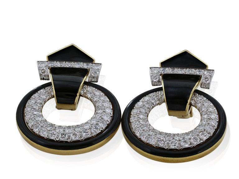 An iconic pair of black enamel coated 18 karat yellow gold and platinum drop hoop earrings with diamond encrusted hoops. by David Webb