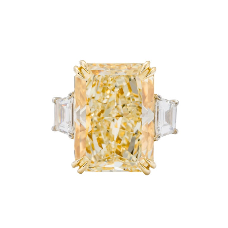 Platinum and 18 karat yellow gold 3 stone ring consisting of 1 radiant cut yellow diamond weighing 17.01 carats with color and clarity of FY/VS2 GIA #5182705391 flanked by 2 trapezoid diamonds weighing a total of 1.27 carats. D VVS2 Size 6.5