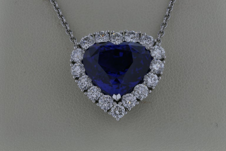 18 karat white gold pendant necklace featuring a 16.86 carat heart shaped sapphire surrounded by 16 round brilliant cut diamonds with a color and clarity of F/G and VS1/VS2, respectively.