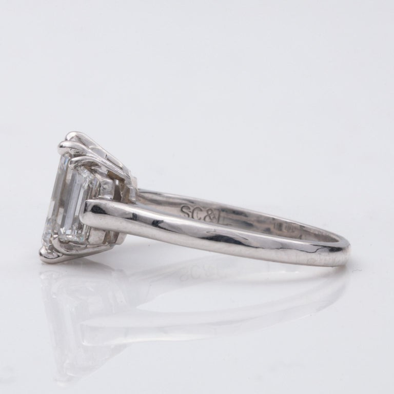 Three Stone Emerald Cut Diamond Ring.  This ring features a center diamond measuring approx. 8.80x6.70x4.2mm, with an approx weight of 2.20ct with an approximate color and clarity grade of F VS1 respectively.