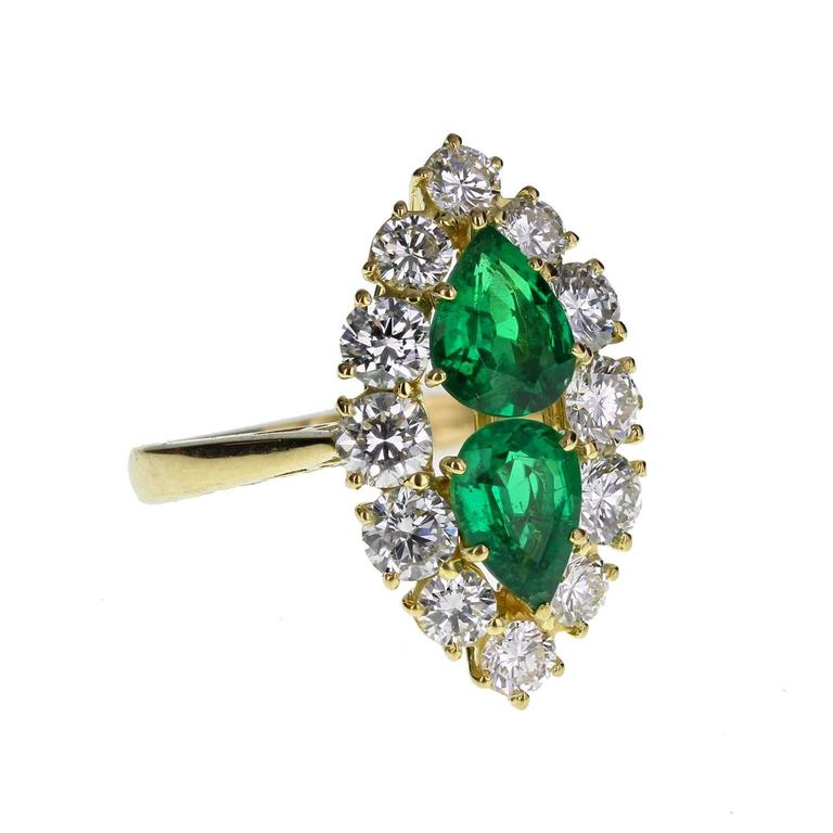 A fine and impressive cocktail ring featuring two deep, bottle-green pear shaped emeralds, surrounded generously with bright and lively diamonds to create a marquise-shaped cluster. Birmingham hallmark. A particularly fine quality ring at an