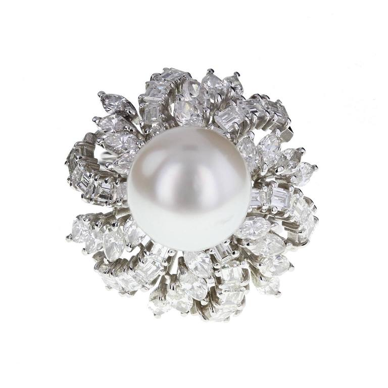 A beautiful cocktail ring centered with a large pearl of good lustre, surrounded by a 'skirt' of alternating rows of marquise and emerald-cut diamonds. Shank comprising five 'wires' of white gold, splitting at the shoulders. An impressive and