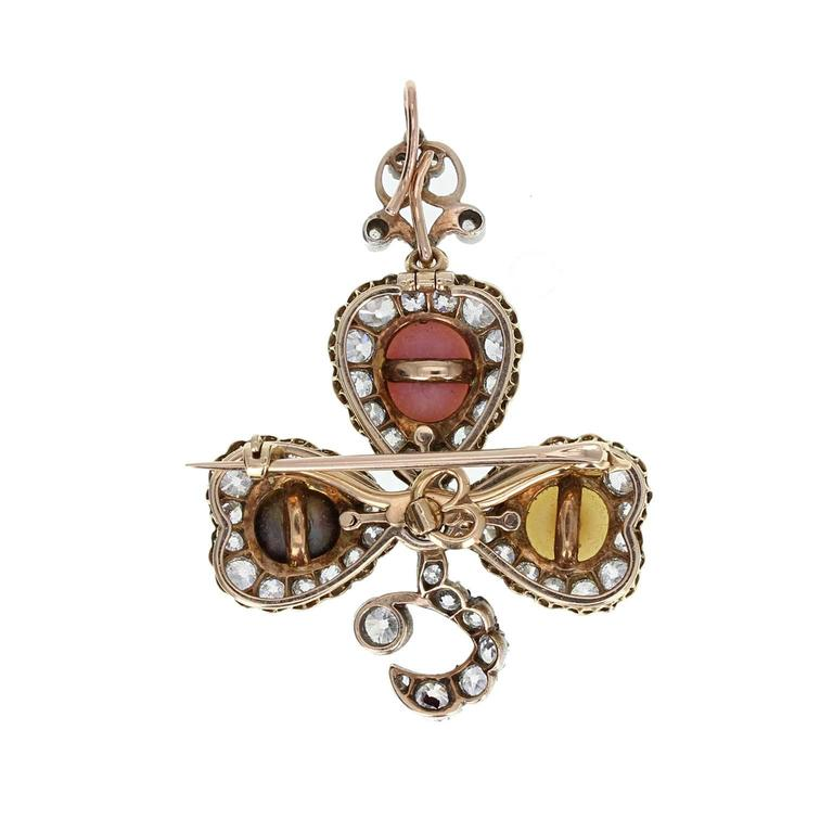 This exquisite antique brooch/pendant in the foliate form of a clover/shamrock, is set with old-cut diamonds and a single natural pearl on each 'leaf'. One pink conch pearl, one black pearl and one white pearl. Crafted in 18 carat gold and sterling