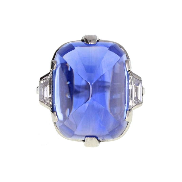 This exquisite Art Deco ring features a stunning 'Sugarloaf' sapphire with unusual and beautiful faceted corners. Accompanied by a certificate stating that the sapphire is a massive 30 carats, is from Ceylon and has not be subjected to any form of