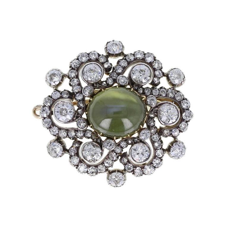 A fine and impressive piece from the Edwardian period. Bright, lively old-cut diamonds, arranged in a pierced, swirling setting, frame a single oval cabochon cat's eye, which displays excellent chatoyancy. Removable brooch fitting to the rear, so