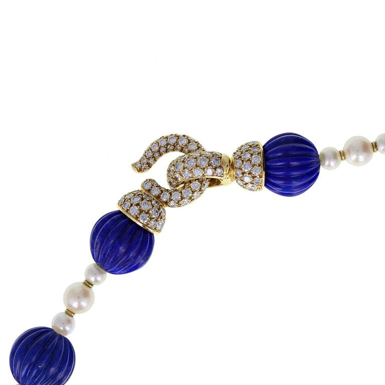 An exquisite sautoir by Cartier Paris. 26 ribbed beads of well-matched lapis lazuli are strung on silk, each interspersed with a trio of pearls, themselves separated by a pair of gold rondels. The eye-and-hook clasp is formed from 18-carat yellow