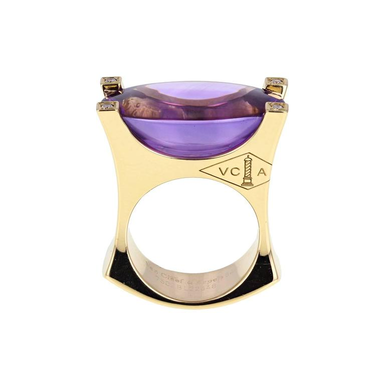 A bold cocktail ring by Van Cleef & Arpels. The central 25 carat oval cabochon amethyst mounted in four heavy claws, each claw set with a single brilliant-cut diamond. VCA logo engraved to the side of the squared shank. Signed VCA and numbered.
