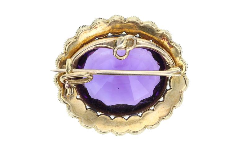 A late Victorian brooch/pendant featuring a large oval amethyst of deep, velvety purple colour, surrounded by a border of 21 seed pearls all mounted in 18 carat gold. Brooch pin fitting that can be removed and a hinged bale so it can be worn as a