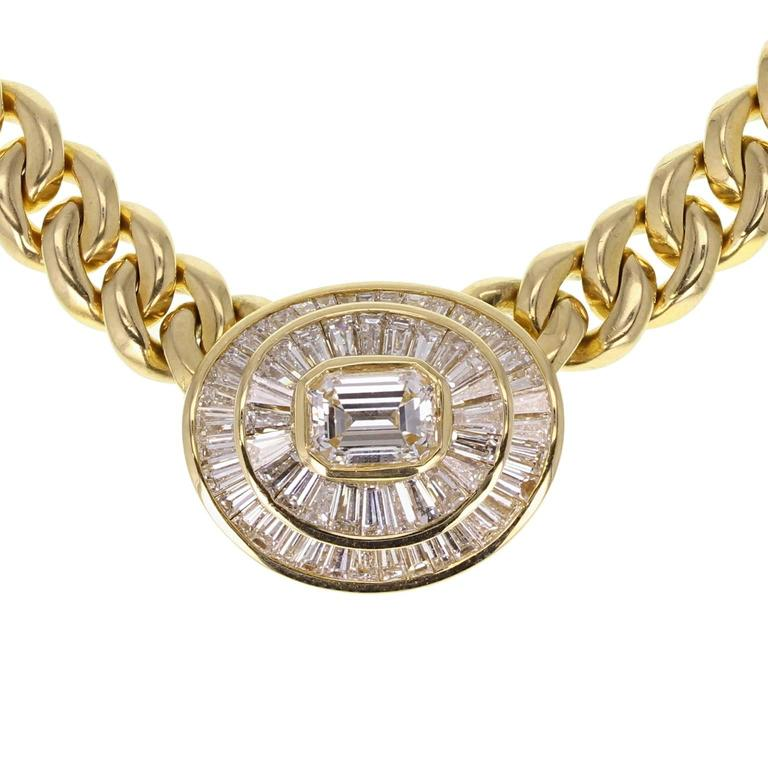 A fine and impressive pendant necklace by Bulgari. The flat curb style 18 carat gold chain leading to an oval pendant. The centre emerald-cut diamond surrounded by a double channel of tapered baguette-cut diamonds to form an oval cluster. A GIA