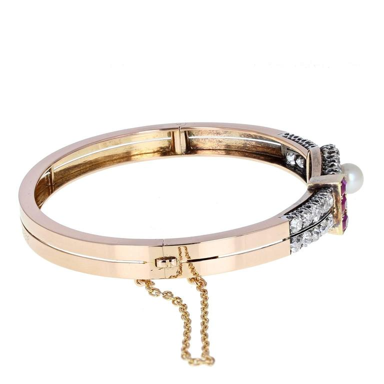 This outstanding quality Victorian bangle is in exceptional condition. Fashioned from 18 carat rose gold, it features a central loop designed setting. A single pearl is mounted, surrounded by a loop of bright and lively old-cut diamonds with
