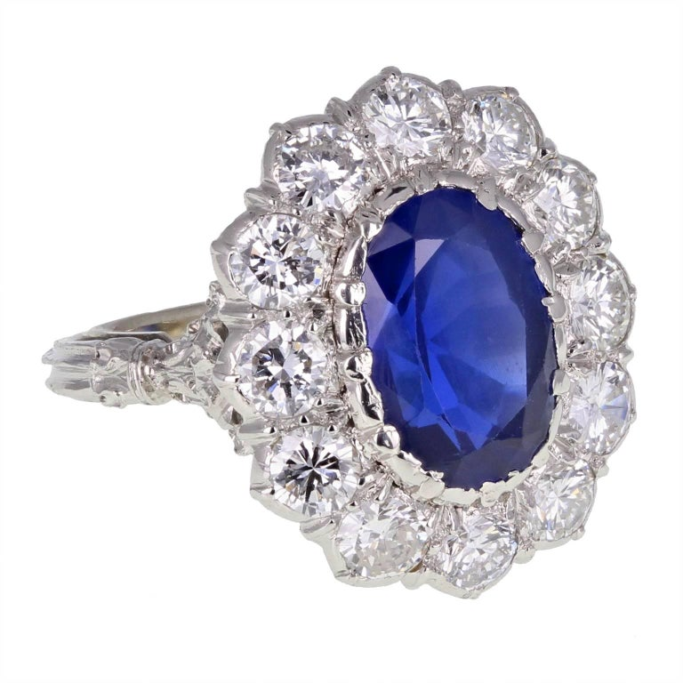 An exquisite Burma sapphire and diamond cluster ring by Buccellati. The oval, unheated sapphire surrounded by bright and lively brilliant-cut diamonds. Highly decorated shoulders and reeded shank. Signed Buccellati. Specifications:   Shank and