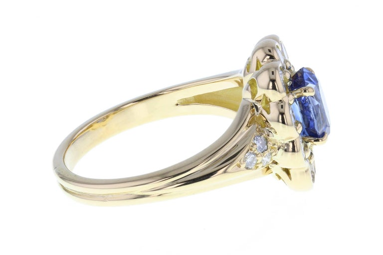 The central oval-cut sapphire exhibits a stunning blue colour with lilac tones. The exceptionally coloured sapphire is mounted in four discreet claws and surrounded by 10 round, brilliant-cut diamonds in a rub-over setting. Some diamond detailing to