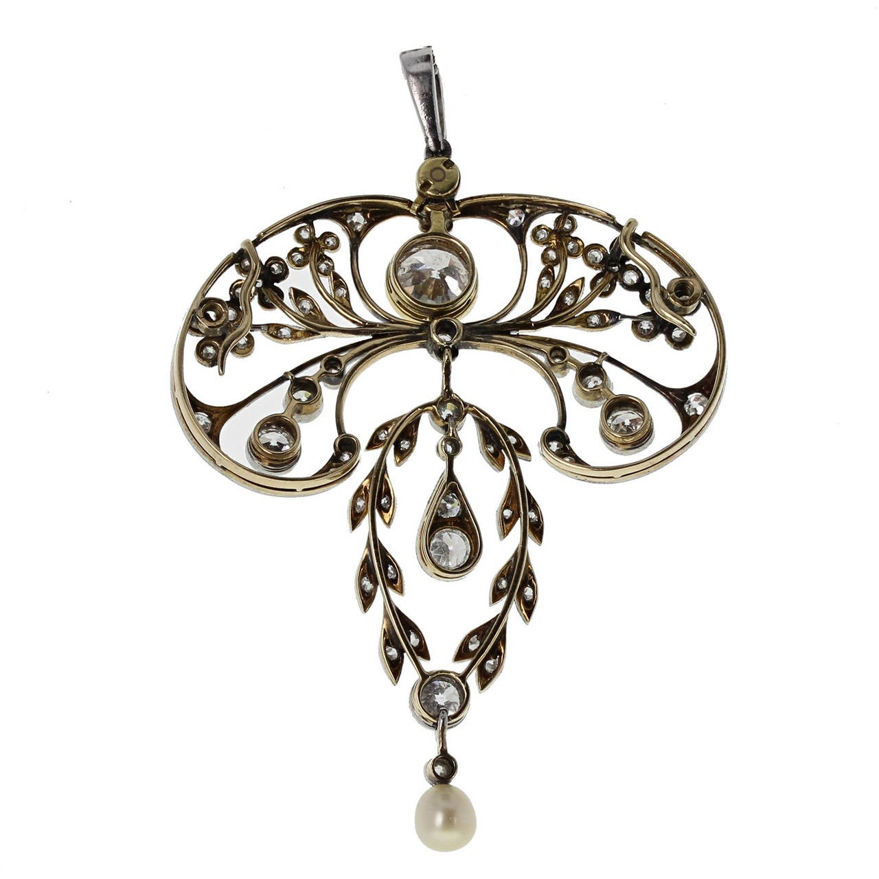 Formed in platinum and 18 carat gold with typical period style and mille-grain edging. A 5mm natural pearl suspended from the bottom articulated wreath section. The central principal diamond weighs approximately 0.75 of a carat, H colour and SI