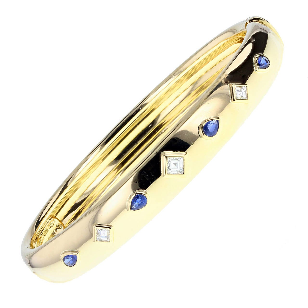 A suite of jewellery comprising a bangle, ring and pair of earrings. Each rubover set with pearshaped blue sapphires and french-cut diamonds. Signed Cartier and numbered.