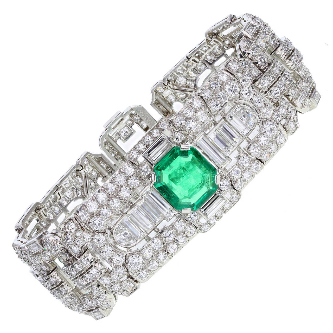 Expertly fashioned from platinum this bracelet comprises of three pierced panels set with baguette and round-cut diamonds in a typical style for the period. Each of the three panels is set with a central very fine quality Colombian emerald. The