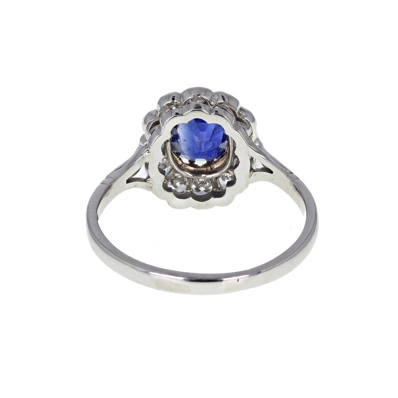 This outstanding cluster ring features a central oval-cut blue sapphire of deep, velvety blue, surrounded by old-cut diamonds to form an oval cluster. Trifurcated shoulders and uniform shank stamped 'plat'. A GCS certificate accompanies the sapphire