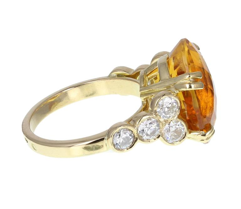 A central faceted oval citrine of stunning vivid orange colour flanked on each side by four round, brilliant-cut diamonds, rubover set on a uniform, squared shank. A fantastically eye-catching ring.   Shank and Setting Tests as 18ct gold