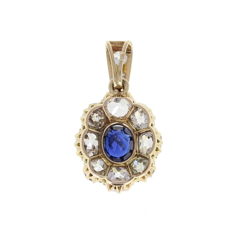 A fine and impressive antique pendant from early 1900s. A central cushion-cut blue sapphire of velvety, deep blue, sits in eight claws, surrounded generously by eight cushion-cut, bright and lively diamonds to form an oval cluster shape. Suspended