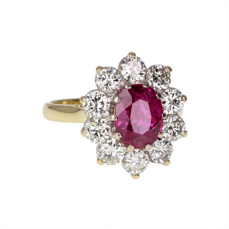 A fine, classic cluster ring featuring a central oval ruby weighing 2.40 carats, surrounded by ten brilliant-cut diamonds to form an oval shaped cluster. Claw set in a traditional basket setting. Simple and elegant, with a fine polished shank.