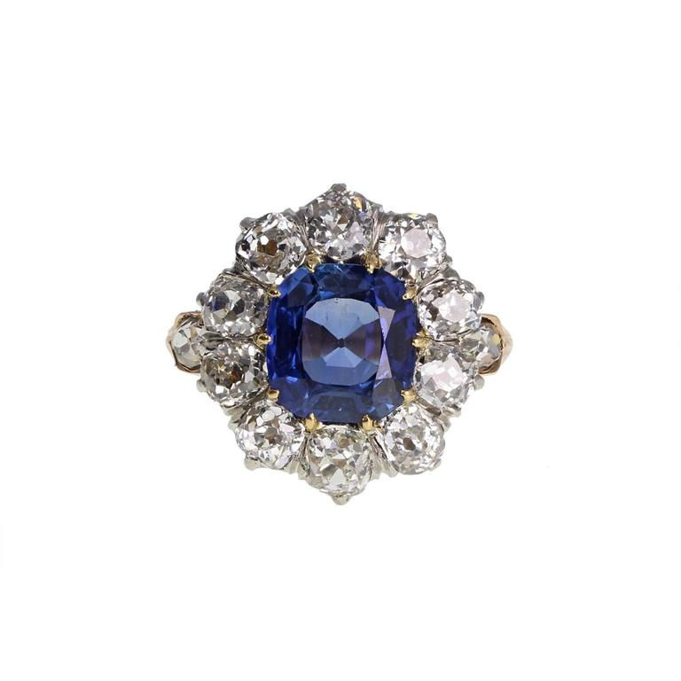 A particularly pleasing antique sapphire and diamond cluster ring. The central cushion-cut sapphire is of a beautiful, even and intense cornflower blue. Mounted in ten claws and surrounded by ten old mine-cut diamonds of bright and lively nature. A