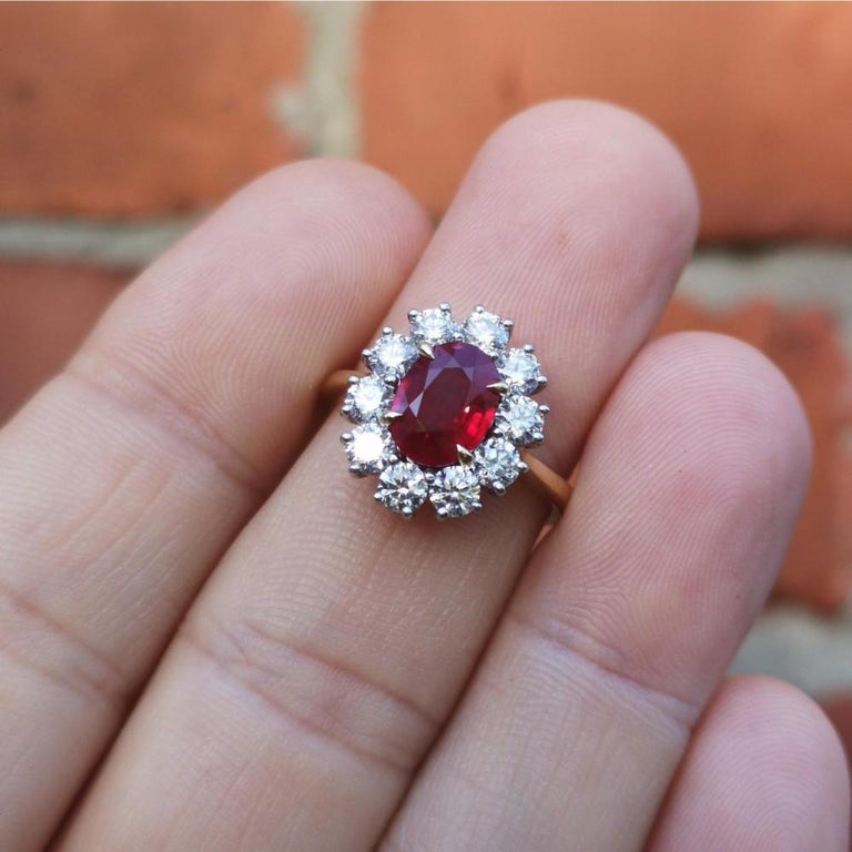 A very fine quality ruby and diamond cluster ring. The central, exceptional colour, blood red Burma ruby sits in four, beautifully pointed claws. Surrounded by 10 bright and lively brilliant-cut diamonds to form a cluster. A simple polished gold