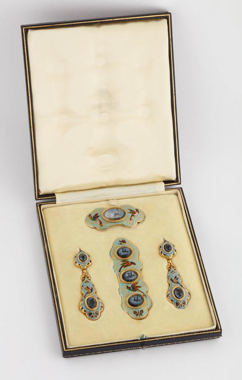 A beautiful pair of Swiss enamel pendant earrings, along with a matching brooch and large sash clasp, in 18K gold with opaque and foil enamel birds and butterflies, set with 8 antique intaglio stone carvings. The earrings made in two pieces allowing