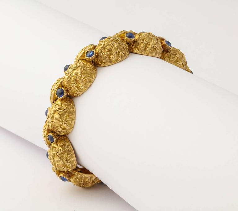 A modern and elegant 1970s bracelet from Cartier-Paris, of unusual design and  deeply textured finish, the quarter round segments of 18K gold each set with a cabochon sapphire, and hinged to move independently and comfortably around the wrist. 7 1/2