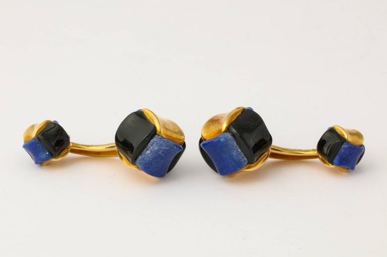 Handsome and one-of-a-kind pair of cufflinks by Angela Cummings, custom ordered c1985, of 18K gold set with carved lapis lazuli and black jade, with an accent of translucent brown enamel in the connecting bar. Marked: Angela Cummings 18K. Largest
