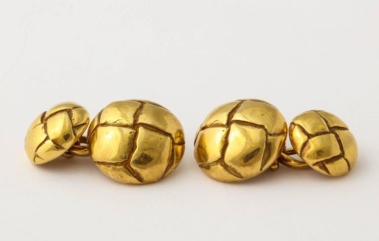 A handsome and sporty pair of Tiffany cuff links of 18K gold, formed as woven  leather covered buttons. .855 grams, 5/8 inch diameter. Marked 1979, with Tiffany and gold marks.