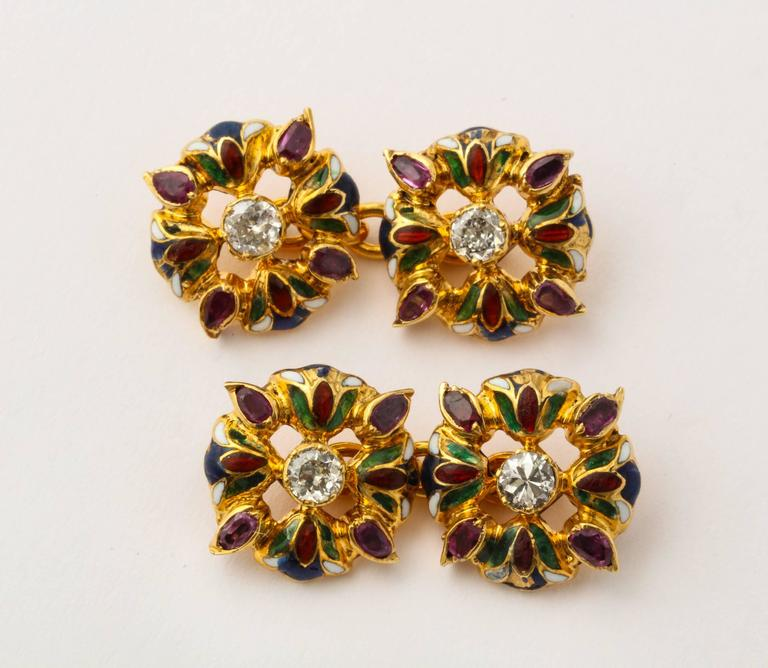 A beautiful Art Nouveau Egyptian style formal set of double side cufflinks and three studs in 18K gold, each element formed as four lotus flowers with green and red enameled petals, each centered with a diamond and a ruby set between each flower.