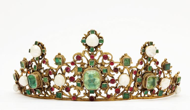 Circa 1860 Austro-Hungarian gemstone tiara of gold gilt silver filigree set with emeralds and rubies and highlighted with natural pearls, in original leather travel case. Unidentified marks, 65 grams, 2 1/2 inches x 7 1/2 inches. From a Palm