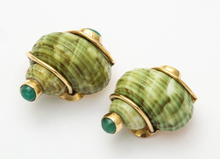Smart and very wearable size of the classic Seaman Schepps ear clips featuring  natural green sea shells mounted in 18K gold set with emerald cabochons. Marked Seaman Schepps, P.S.V. (Patricia Vail), and 18K. 1 1/4 inches. 22.3 grams.