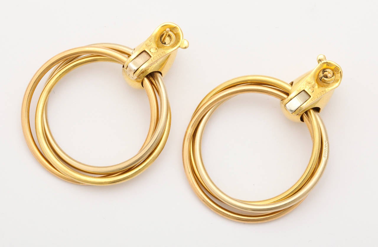 Elegant for day or evening, these simple Cartier-Paris hoops are fashioned of 18K yellow gold, but have the appearance of a two-tone finish. The hoops move  freely of each other, but are interlinked to move gently as a unit. Multiple gold, maker,