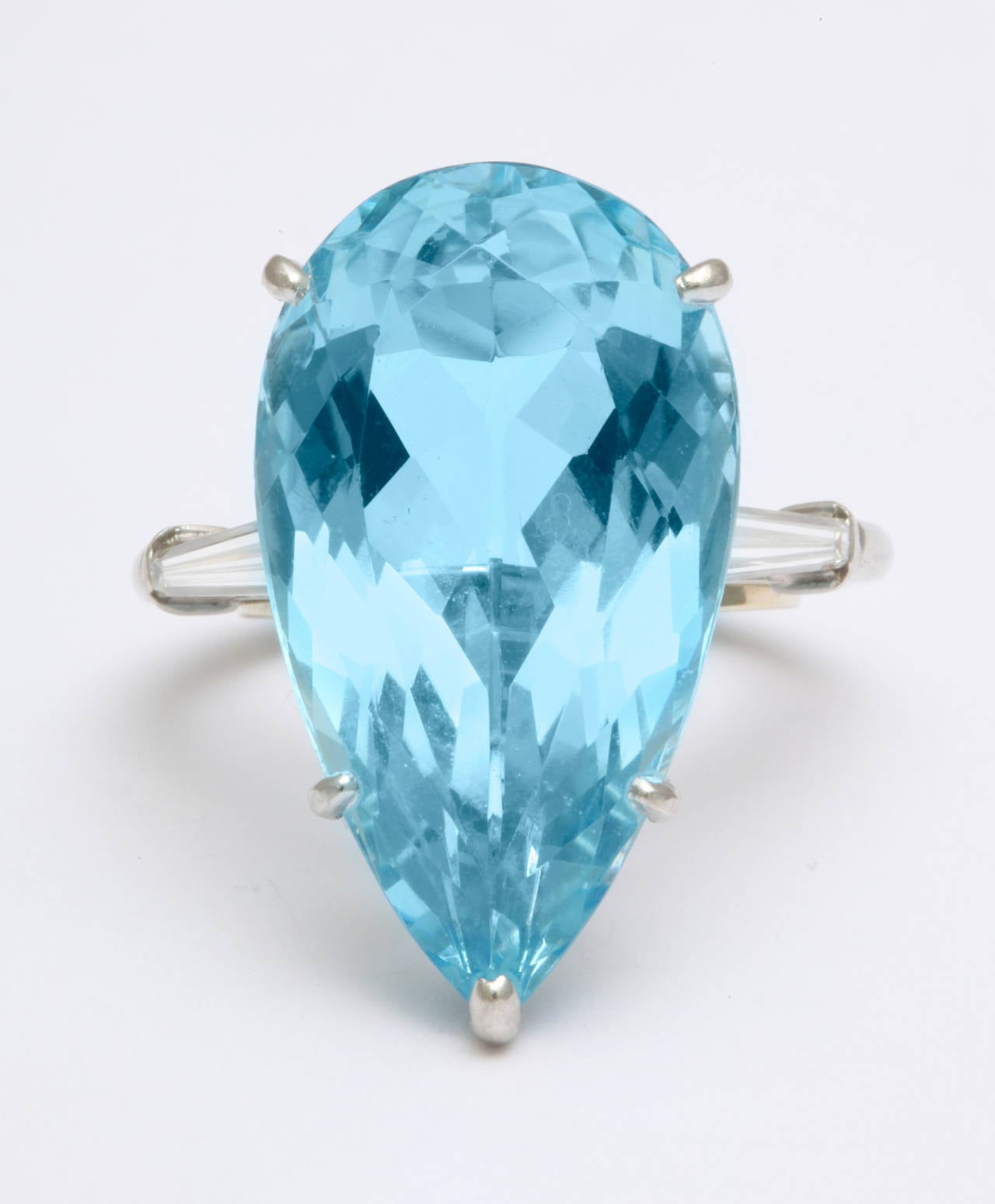 A glamorous 1950s platinum ring by Cartier holding a pear shape 16.88ct natural aquamarine, with long slender tapered baguette diamonds on each side.  Signed Cartier. Aqua measures 1 inch. Currently fits a size 6 finger. With original box, and an