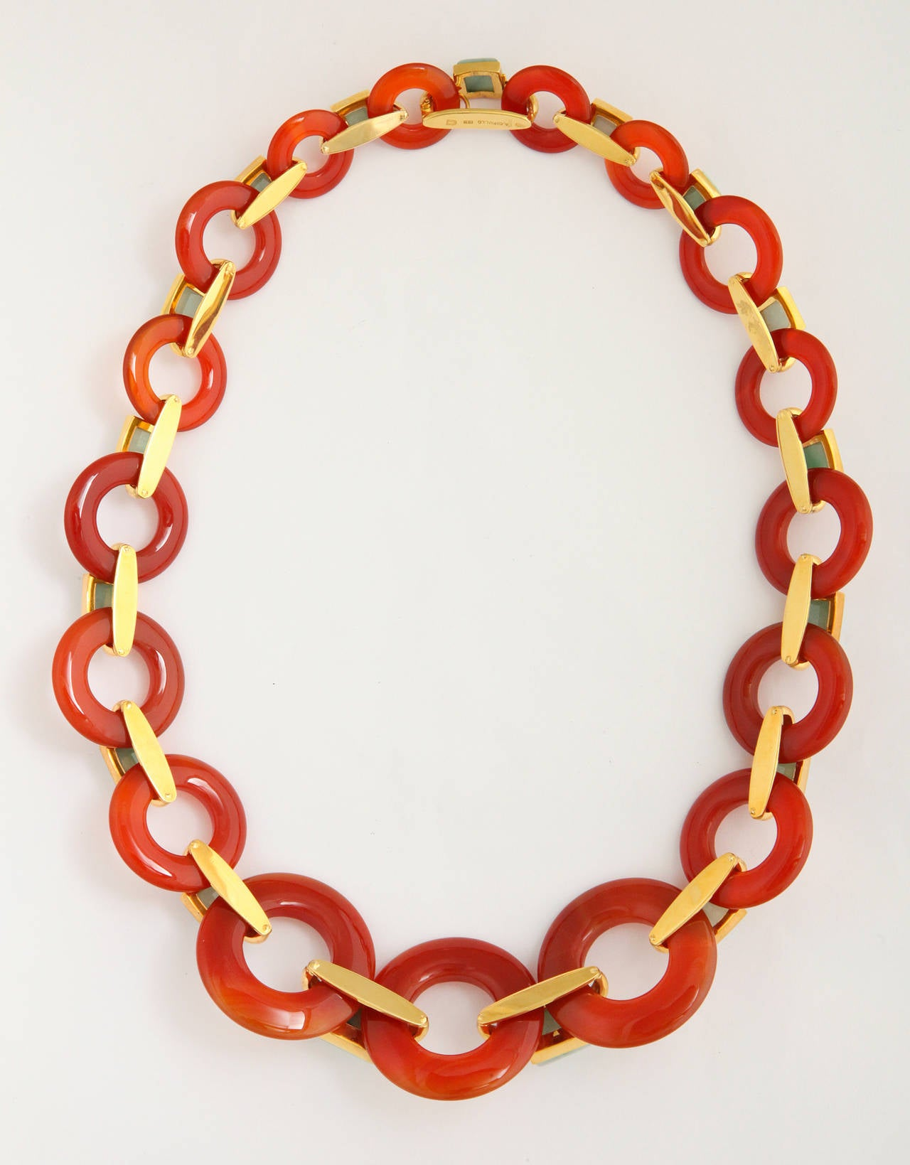 "A stylish and fashion-current 1970s necklace by reknown jewelry maker Aldo Cipullo incorporating large graduated ""life savers"" of hand carved carnelian, connected by 18K gold links set with pyramid cut mottled light green jade elements."