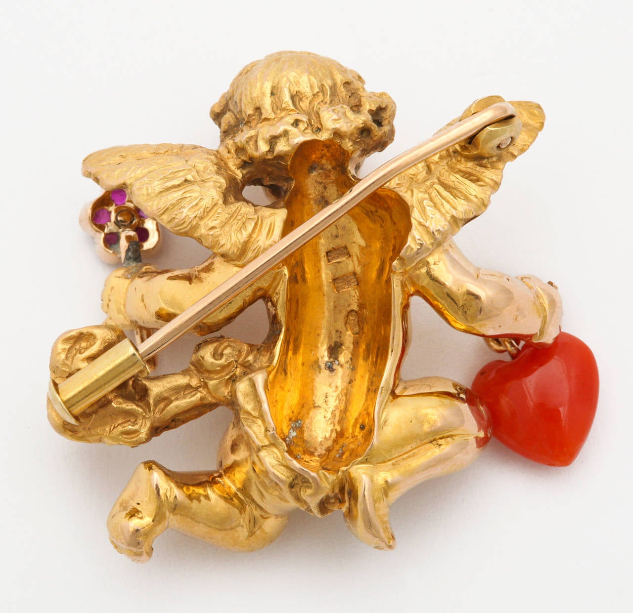 A charming and elegant figural brooch by the renown Viennese firm of Paltscho. A fine 18K gold representation of a cherub in flight, offering a ruby and diamond set flower in one hand, and a natural red coral heart in the other. Inspired by a