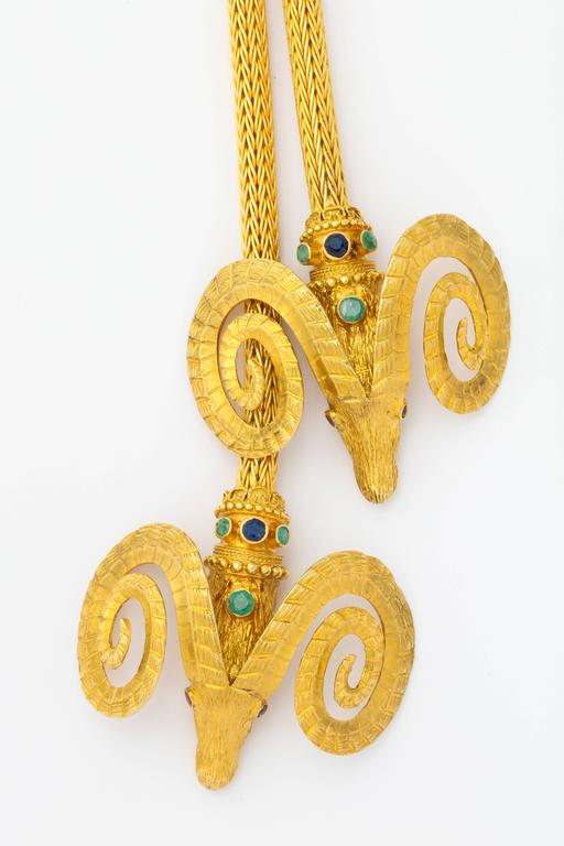 A handsome 1960s 18K gold necklace by Lalaounis, based on a design motif found in Greek antiquity of the ram's head (symbol of prosperity, set with sapphires, emeralds and rubies, as the decorative ends of a generous braid-woven gold rope with