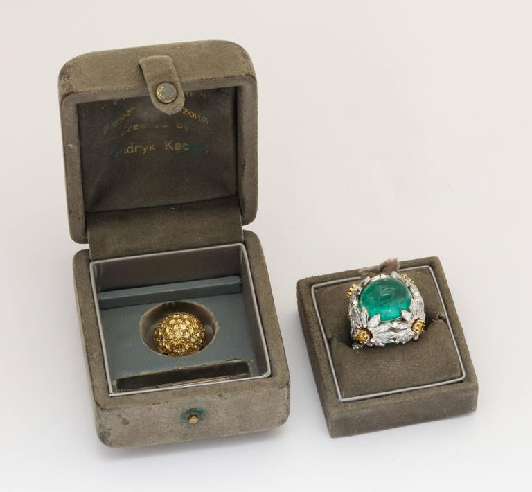 Two rings in one - a unique cocktail ring by renown musician/bow maker/jewelry artist Hendryk Kaston of platinum and 18K gold as four large desert flowers set with 4.20cts of round and marquise cut diamonds GH/VS framing a 23ct M12 cabochon emerald