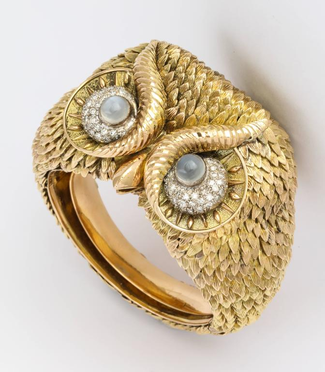 Made to order in the 1960's, this exceptional figural owl bracelet is completely hand crafted of 14K gold (150 grams), with each feather individually formed and attached to form a sculpture for the wrist, set with star moonstones with diamond