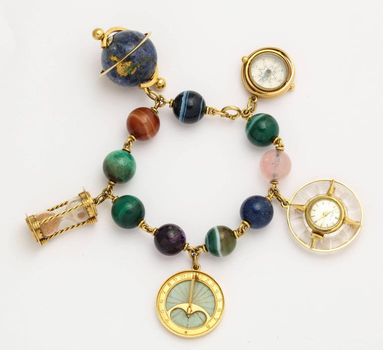 A remarkable find - This Gubelin charm bracelet of 18K gold and large hard stone beads including banded agate, lapis, malachite and rose quartz, holds five beautifully crafted 18K gold movable charms: 1. A spinning globe of lapis with golden