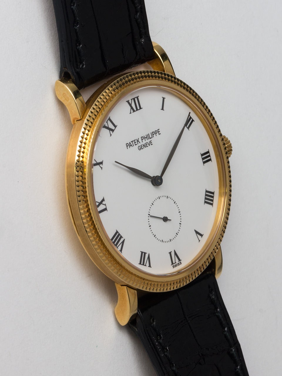 Patek Philippe 18K Yellow Gold Calatrava Wristwatch, Ref. 3919, circa 1990s. Hobnail bezel, calatrava-logo crown, 33mm diameter case with white dial, Roman numerals and leaf hands. 18-jewel manual-wind movement with subsidiary seconds. Classic dress