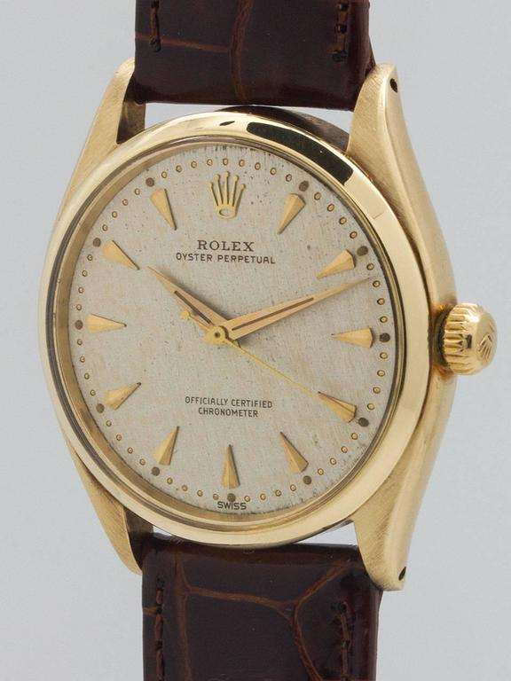 Rolex 14K Yellow Gold Oyster Perpetual Wristwatch ref 6564 serial number 435,xxx circa 1960. Featuring 34mm diameter Oyster case with smooth bezel, acrylic crystal, screw down crown and case back. Featuring an unusual, original matte silvered finely