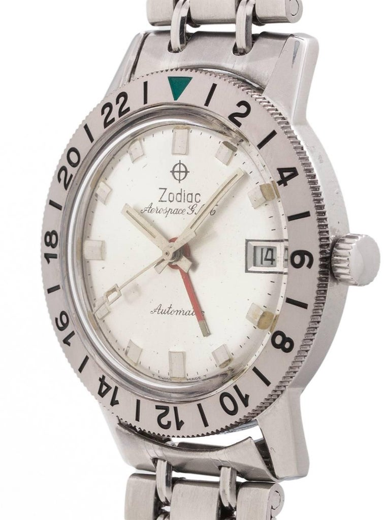 A mint condition Zodiac stainless steel Aerospace GMT circa 1960's with original signed bracelet. Featuring a 36 x 43mm case with rotating 24 hour bezel, minty condition original silvered satin dial with applied geometric silver indexes and
