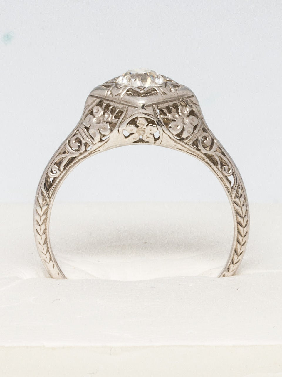 Platinum filigree solitaire ring with center 0.47 carat old European cut diamond, J color and SI clarity. Setting showcases pierced flowers and scrolled detail with hand engraving. Size 6.75 circa 1920's  As a special offering for our 1stdibs