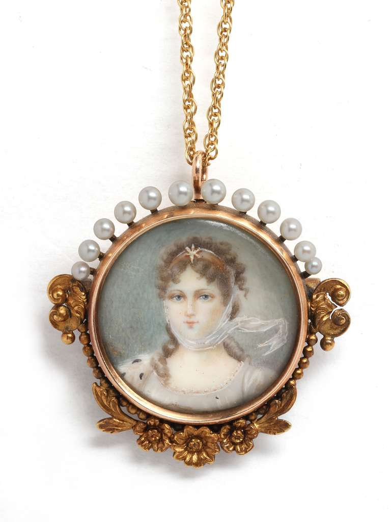 Hand painted miniature portrait of a young, pretty, blue eyed woman with brown curly hair wearing a sheer flowing white scarf. Framed in 14k gold, crowned with little graduated size pearls and foliate design at the bottom. Precious! Can be worn as a