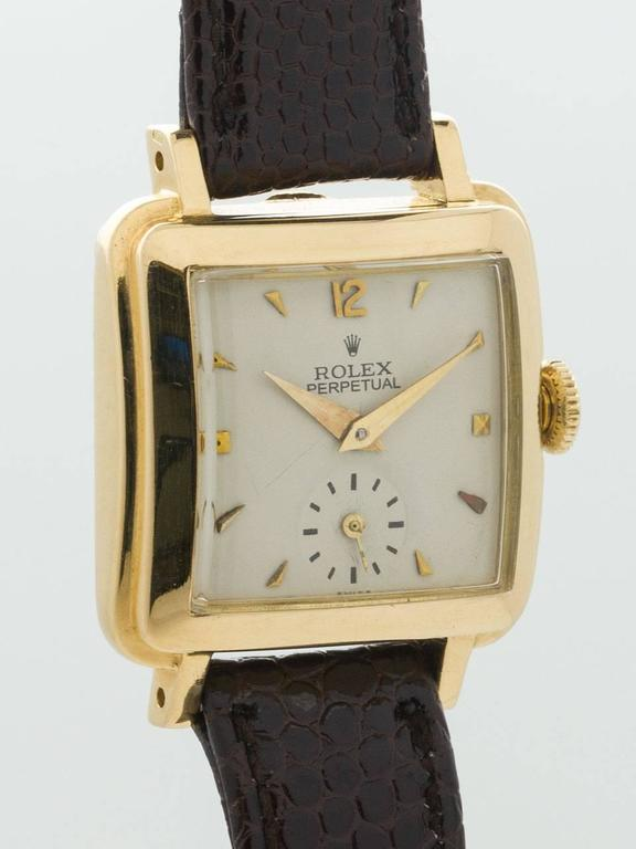 A scarce vintage Lady Rolex Square Bubbleback 18K Yellow Gold Wristwatch ref 4663 circa 1950. Featuring 24.5 X 31mm square, stepped thick case with extended lugs and curved crystal. With very pleasing restored antique white dial with gold applied
