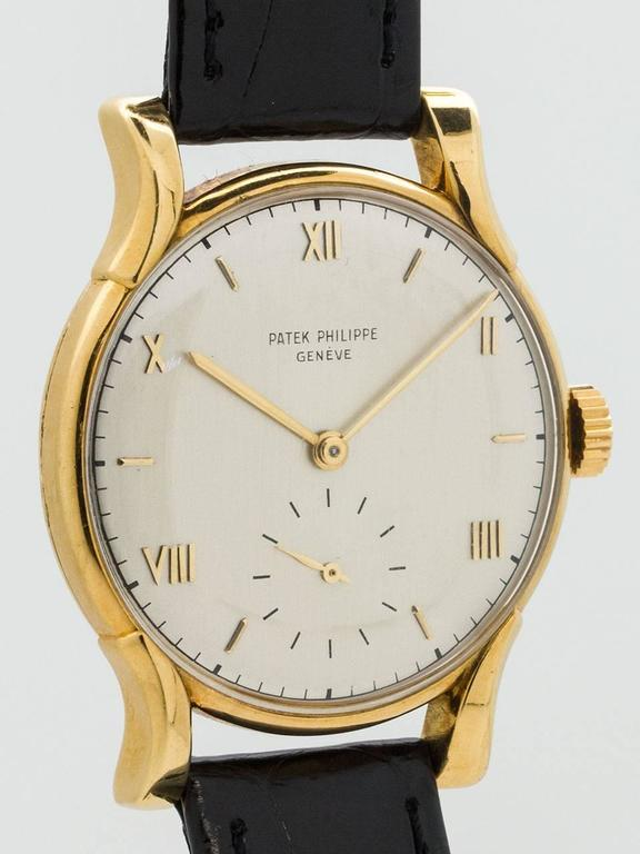 Large and great styling vintage man's wristwatch Patek Philippe 18K Yellow Gold Wristwatch ref 1596 circa 1950. Featuring 35 X 43mm case with heavy bowed lugs and acrylic crystal. Nicely restored silvered satin dial with gold applied Roman number