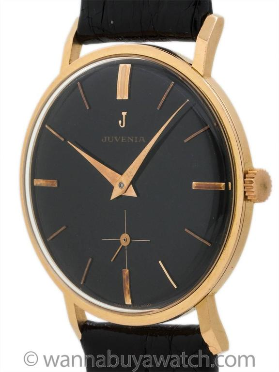Juvenia 18K rose gold man's dress model circa 1960. Featuring 33 x 41mm heavy snap back case with extended faceted lugs. With a beautiful condition glossy black original dial with applied rose indexes, applied Juvenia logo, and with elegant rose